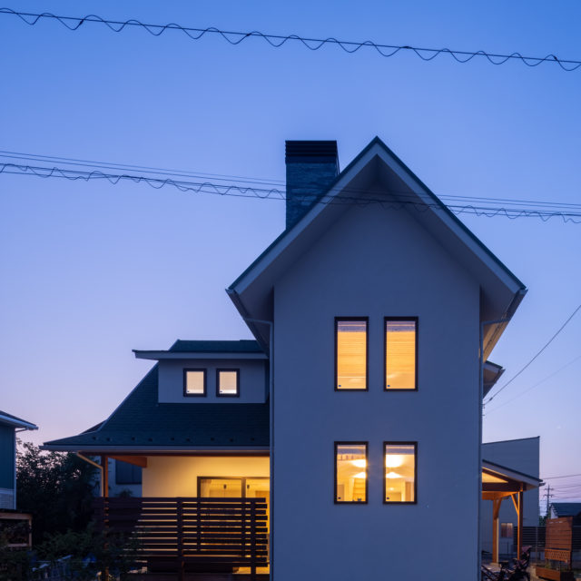 三角屋根と薪ストーブのある北欧デザインの家